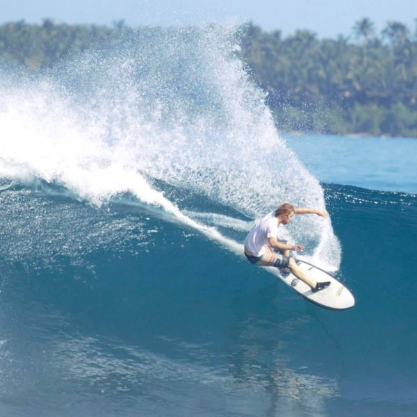 big tom surf instructor at kingsurf surf school in mawgan porth, surfing krui reef in sumatra, indonesia, performing a forehand topturn