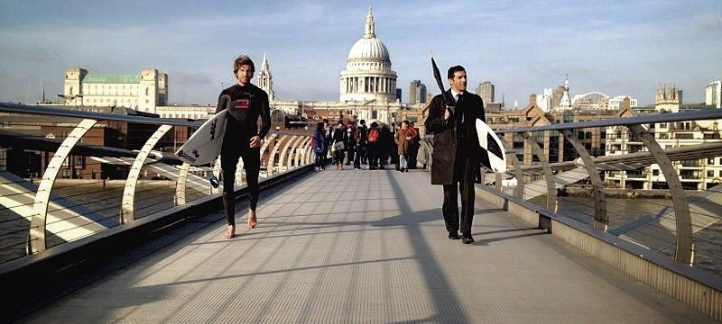 corporate london suit surfing man in wetsuit walking over bridge team building activities
